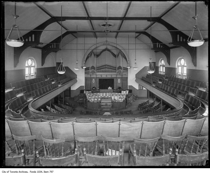 Interior of church sanctuary with pipe organ centred in chancel, showing gas dome ceiling fixtures hanging over 3-sided balcony. - [ca. 1917]