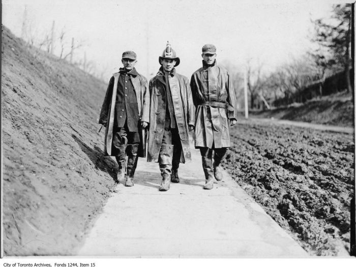 Three firemen walk beside muddy Lansdowne Avenue, north of Davenport Road. - [between 1910 and 1920]