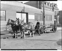 Horse-drawn cartage wagon in yard of Hendrie and Co. Ltd. storage warehouse
