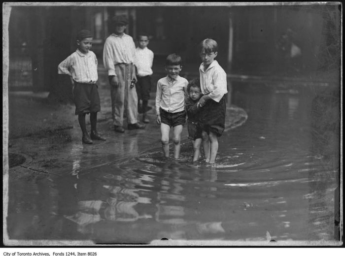 Children in a flooded slum street. - [ca. 1914]