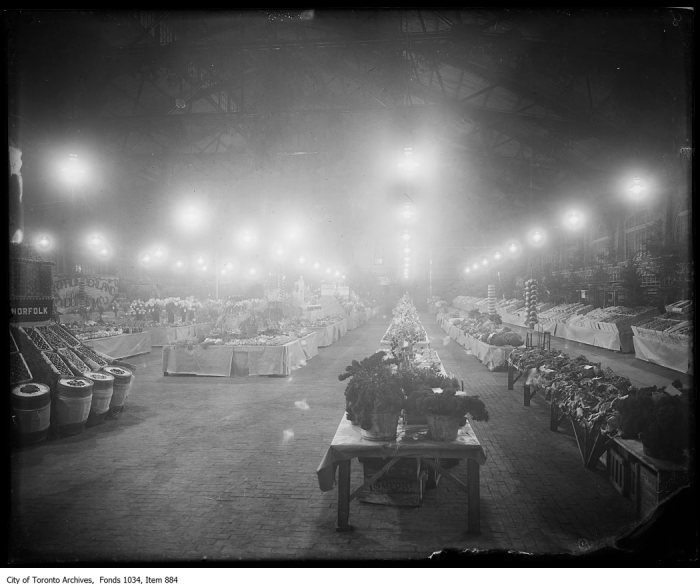 Interior of North St Lawrence Market on market day, lit with Humphrey gas arc lamps - note brick floor and viewing balcony with chairs on right. - [ca. 1917]