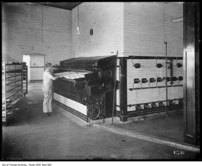 Baker putting loaves into traveling bake ovens at Ideal Bread Bakery. - [ca. 1923]