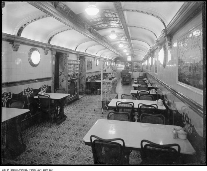 Interior of long narrow restaurant with bentwood chairs, mosaic floor and ceiling reminiscent of a railway car. - [ca. 1916]
